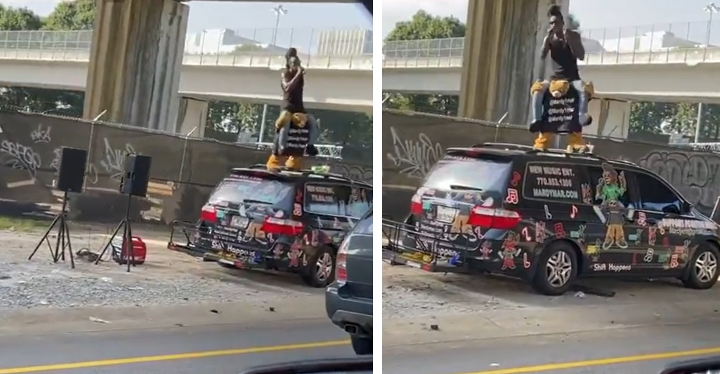 Guy Performs On The Side Of The Freeway While Standing On Top Of His Van